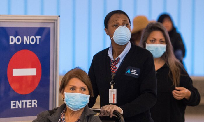 Passengers wear face masks to protect against the COVID-19 (Coronavirus) after arriving at the LAX airport in Los Angeles, Calif., on March 5, 2020. (MARK RALSTON/AFP via Getty Images)