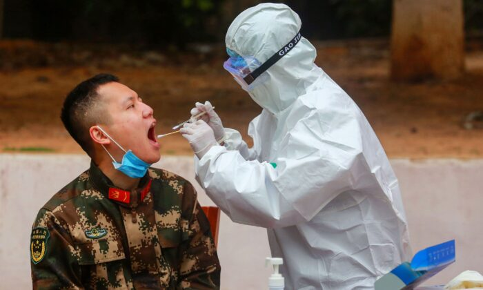 A medical staff member collects samples from Chinese paramilitary police officers to be tested for COVID-19, in Shenzhen, China, on Feb. 11, 2020. (STR/AFP via Getty Images)