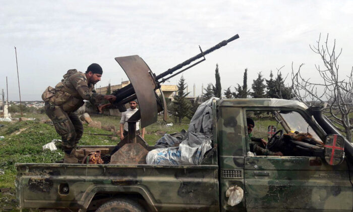 Syrian army soldiers gesture from a military vehicle in southern Idlib province, Syria, on March 5, 2020. (SANA/File/Handout via Reuters)