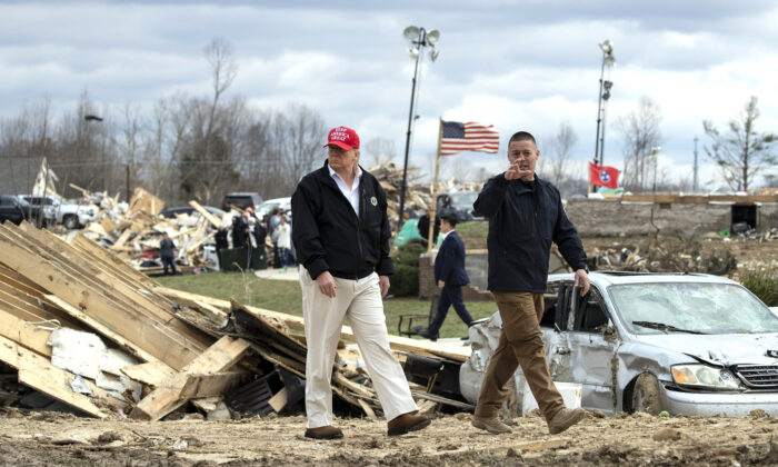 President Donald Trump speaks to Mike Herrick of the Putnam County Rescue Squad as he tours damage from a recent tornado in Cookeville, Tenn., on March 6, 2020. (Alex Brandon/AP Photo)