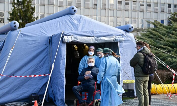 A man receives assistance in the a pre-triage medical tent in front of the Cremona hospital, in Cremona, northern Italy, on March 4, 2020. (Miguel Medina/AFP via Getty Images)