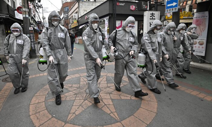 South Korean soldiers wearing protective gear spray disinfectant to help prevent the spread of the COVID-19 coronavirus, at a shopping district in Seoul on March 4, 2020. (Jung Yeon-Je/AFP via Getty Images)