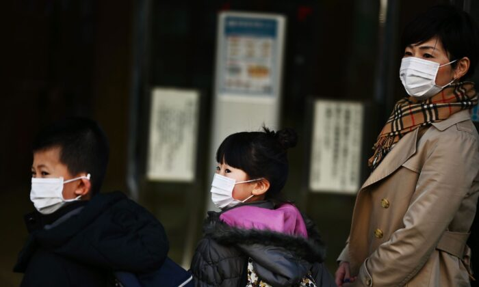 A Japanese woman and her daughter and her son arrive at her work place in Tokyo on March 6, 2020. (Charly Triballeau/AFP via Getty Images)