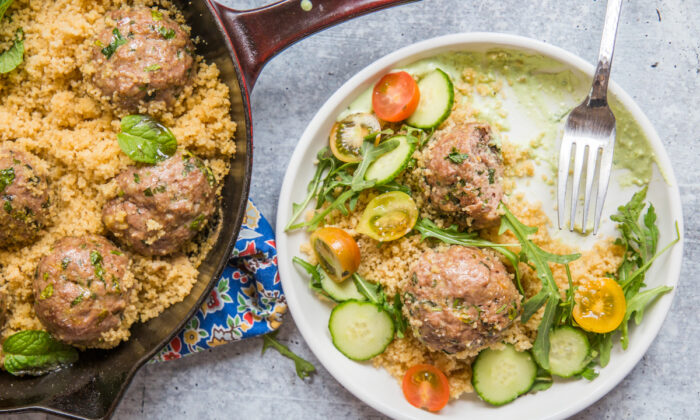 A generous swipe of whipped feta preps the plate for the rest of the meal: couscous, meatballs and crisp veggies, and plenty of fresh herbs. (Caroline Chambers)