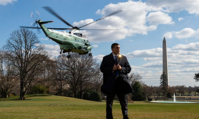 A Secret Service agent stands on the South Lawn of the White house as Marine One helicopter lifts off with US President Donald Trump on board in Washington on Feb. 29, 2020. (Roberto Schmidt/AFP via Getty Images)