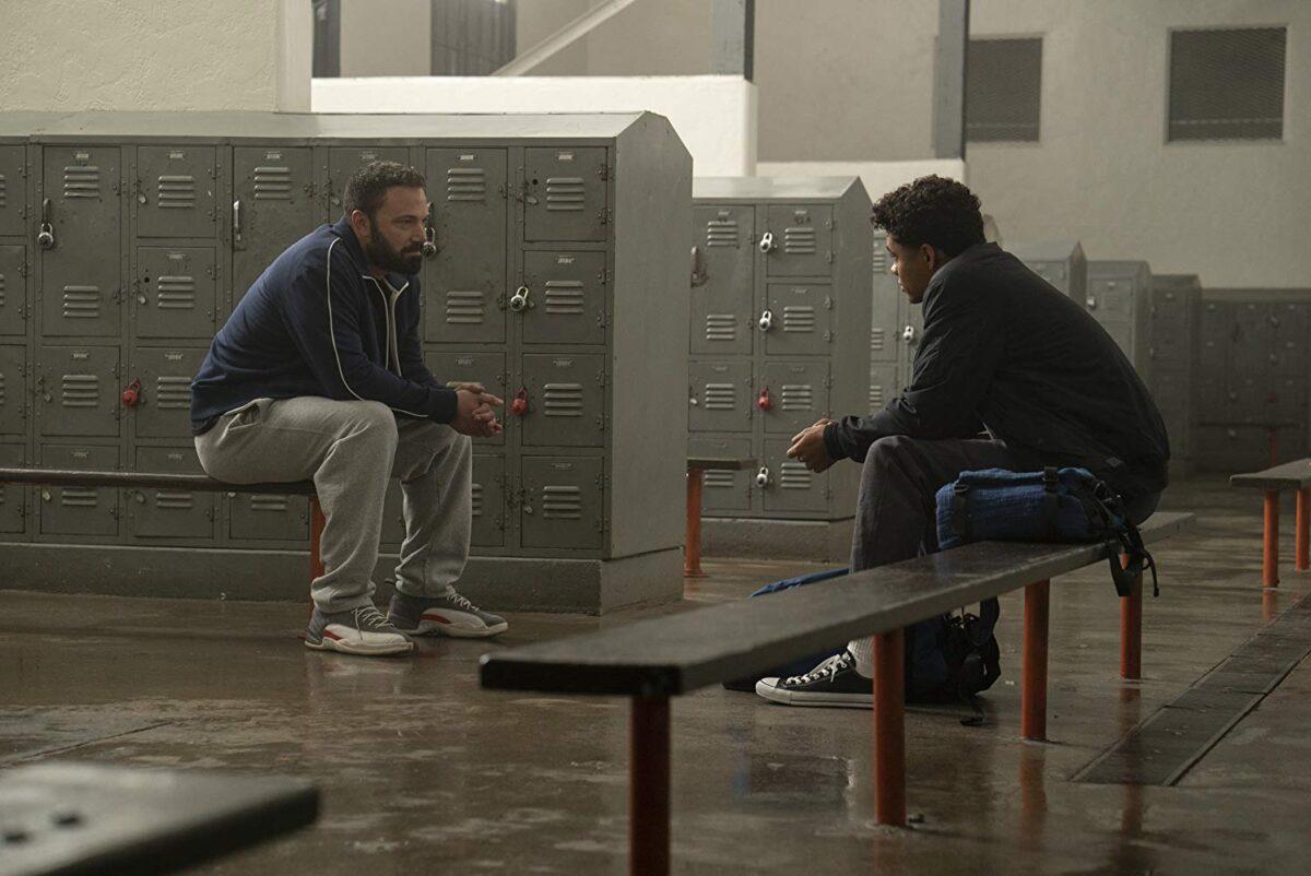 man talking to high school student in lockerroom