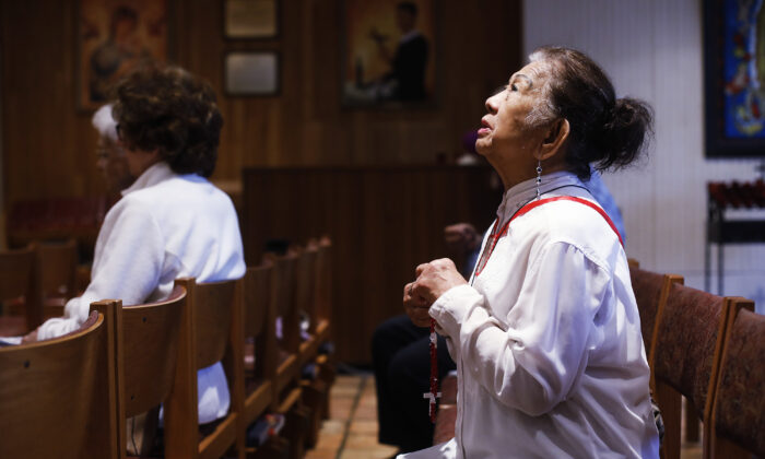 Esther Gianan, a retired registered nurse, prays for those who are affected by the coronavirus during Mass at St. Lawrence Catholic Church in Tampa, Fla., on March 6, 2020. (Octavio Jones/Tampa Bay Times via AP)