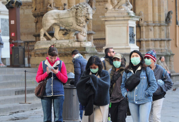 People wearing protective masks walk through Florence