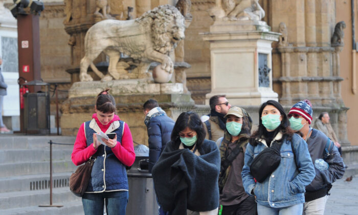 People wearing protective masks walk through Florence as Italy battles a coronavirus outbreak, in Florence, Italy, on March 7, 2020. (Jennifer Lorenzini/Reuters)
