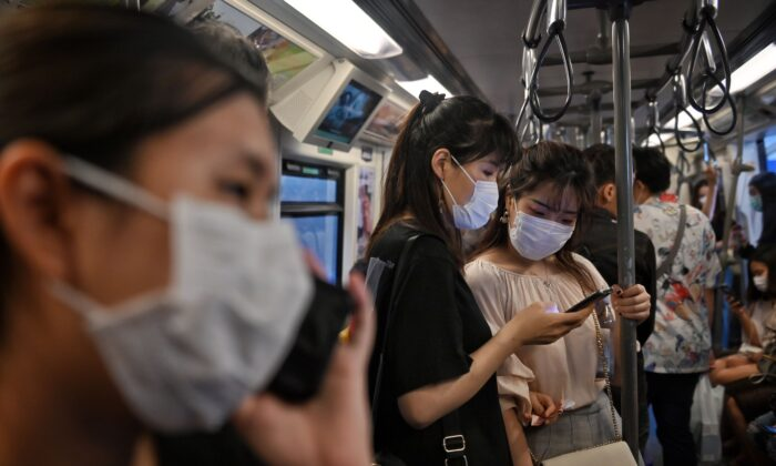 People wearing face masks ride the BTS Skytrain station in Bangkok on March 6, 2020. (Lillian Suwanrumpha/AFP via Getty Images)