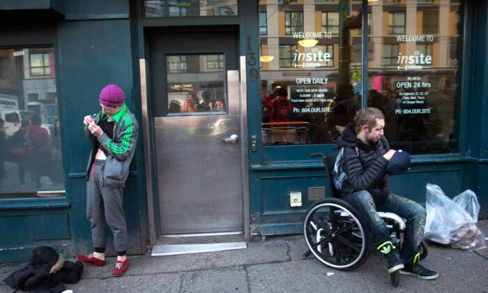 A woman prepares to inject herself with an unknown substance as a man sits in a wheelchair outside Insite, the supervised drug consumption site in Vancouver's Downtown Eastside on Feb. 21, 2017. (The Canadian Press/Darryl Dyck)