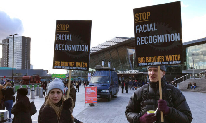 Rights campaigner Silkie Carlo (L) demonstrates in front of a mobile police facial recognition facility outside a shopping centre in London, England on Feb. 11, 2020. (Kelvin Chan/AP Photo)