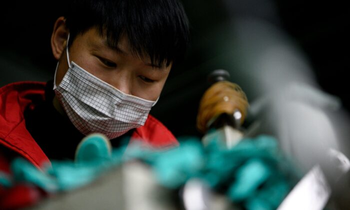 A worker wearing a face mask makes insoles at the Zhejiang Xuda Shoes Co. factory in Wenzhou, China, on Feb. 27, 2020. (Noel Celis/AFP via Getty Images)