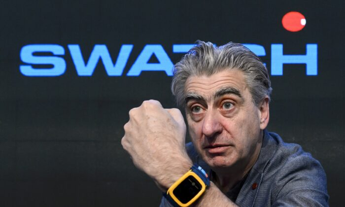 Swiss watchmaker Swatch Group CEO Nick Hayek shows the Swatch Touch Zero One wristwatch during a press conference in Corgemont, Switzerland, on March 12, 2014.  (Fabrice Coffrini/AFP via Getty Images)