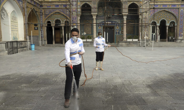 Workers disinfect the shrine of the Shiite Saint Imam Abdulazim to help prevent the spread of the new coronavirus in Shahr-e-Ray, south of Tehran, Iran, March, 7, 2020. (AP Photo/Ebrahim Noroozi)