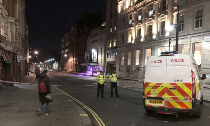 Police stand guard by a cordoned off area after an incident in Westminster, London, UK., on March 9, 2020.  (Scott D'Arcy/PA via AP)