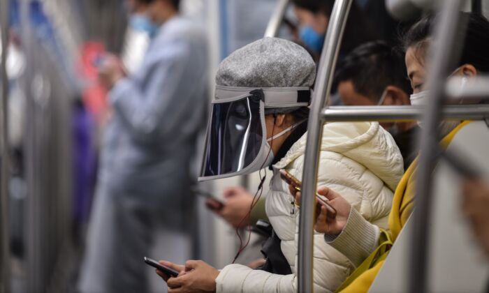 A woman wearing a plastic face cover and a mask travels on a subway train Shanghai, China on March 5, 2020. (HECTOR RETAMAL/AFP via Getty Images)