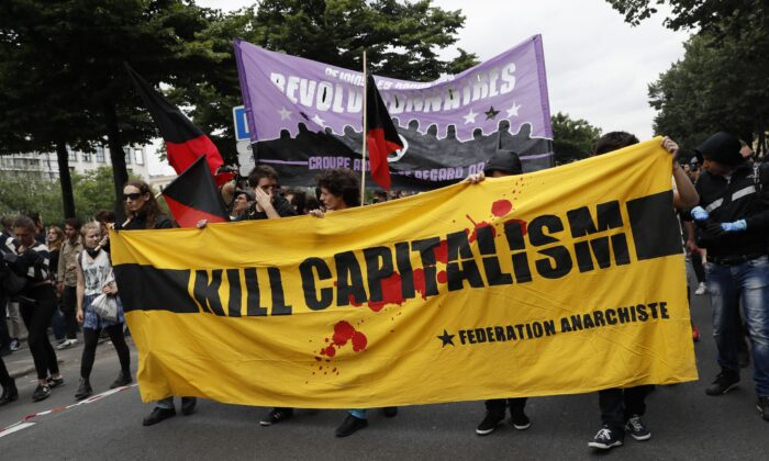 "People hold a banner reading ""Kill capitalism"" during a demonstration against the series of controversial labour reforms in Paris on June 28, 2016. (Thomas Samson/AFP via Getty Images)"