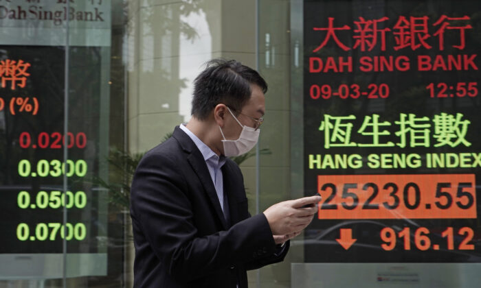 A man walks past an electronic board showing Hong Kong share index outside a local bank in Hong Kong, on March 9, 2020. (Kin Cheung/AP Photo)
