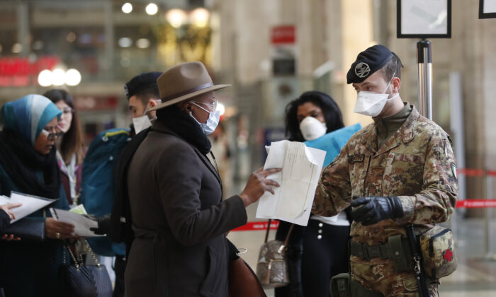 Police officers and soldiers check passengers leaving from Milan main train station in Italy on March 9, 2020. (Antonio Calanni/AP Photo)