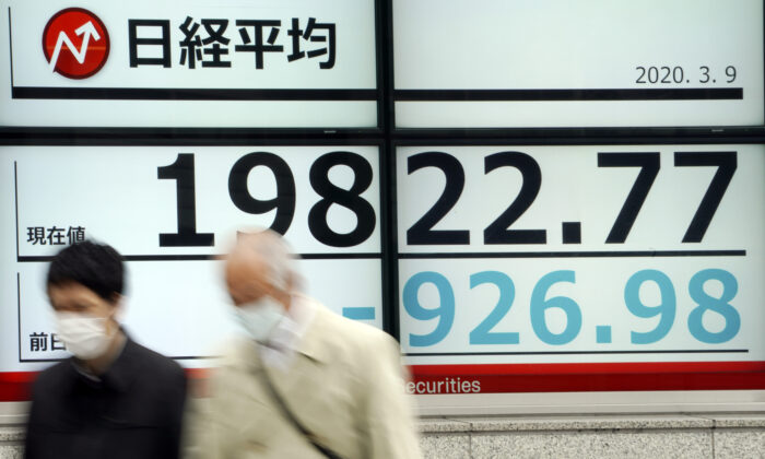 Men walk past an electronic stock board showing Japan's Nikkei 225 index at a securities firm in Tokyo, Japan, on March 9, 2020. (Eugene Hoshiko/AP Photo)