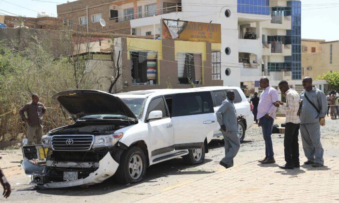 Sudanese policemen stand around vehicles that were part of Prime Mister Abdalla Hamdok's motorcade in Khartoum, Sudan, on March 9, 2020. (Marwan Ali/AP Photo)