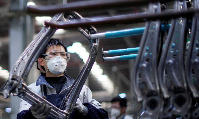 An employee wearing a face mask works on a car seat assembly line at Yanfeng Adient factory in Shanghai, China, as the country is hit by an outbreak of a novel coronavirus, on Feb. 24, 2020. (Aly Song/Reuters)