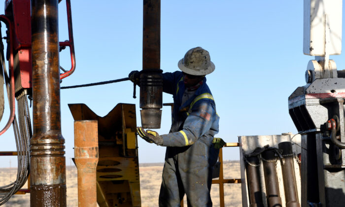 An oil worker removes a thread cap from a piece of drill pipe on a drilling lease owned by Elevation Resources near Midland, Texas, on Feb. 12, 2019. (Nick Oxford/Reuters)