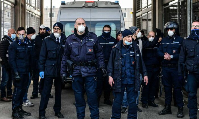 Prison Police officers stand guard after an ambulance (Rear) entered the SantAnna prison during a protest of inmates' relatives in Modena, Emilia-Romagna, in one of Italy's quarantine red zones on March 9, 2020. (Piero Cruciatti/AFP via Getty Images)