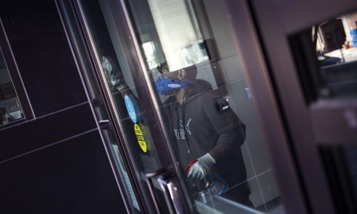 A worker disinfects the front doors of the School Without Walls High School, which was closed today after a member of the school's staff reported close contact with a person who tested positive for coronavirus, in Washington on March 9, 2020. (Win McNamee/Getty Images)