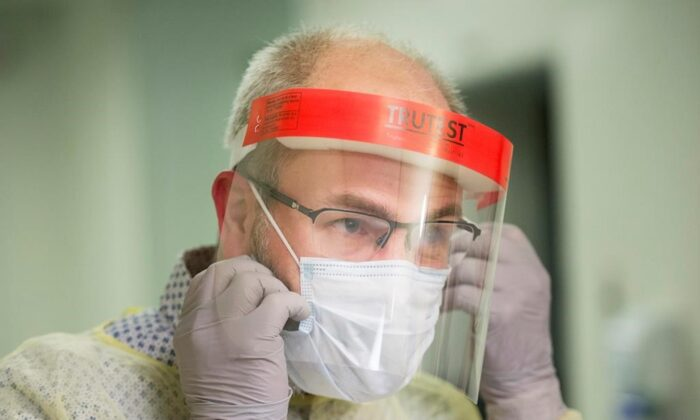 A man demonstrates how to put on a mask and other protective clothing during a tour of a COVID-19 evaluation clinic in Montreal, on March 10, 2020. (Graham Hughes/The Canadian Press)