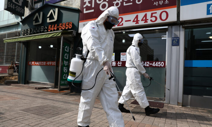 South Korean soldiers, wearing protective gear, spray antiseptic solution to guard against the coronavirus along a street in Gangnam district in Seoul, South Korea, on March 9, 2020. (Chung Sung-Jun/Getty Images)
