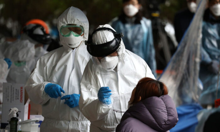 Medical staff wearing protective gear take samples from people at a building where 46 people were confirmed to have the CCP virus, at a temporary test facility in Seoul, South Korea, on March 10, 2020. (Chung Sung-Jun/Getty Images)