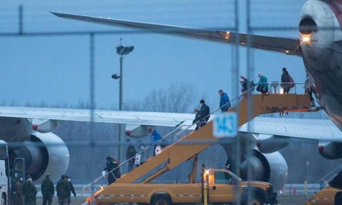 Passengers step off a plane carrying Canadians back from Oakland, Calif. from the Grand Princess cruise ship, after it arrived at Canadian Forces Base Trenton in Trenton, Ont., on March 10, 2020. (The Canadian Press/Lars Hagberg)