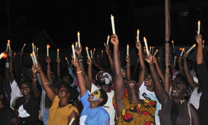 Ugandans hold candles during the Mara Mara peace festival in Kampala, Uganda on March 7, 2020, (Ronald Kabuubi/AP)