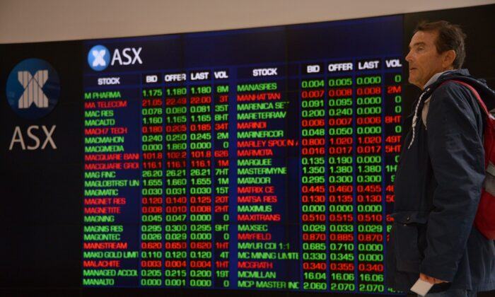 A visitor to the Australian Securities Exchange (ASX) looks at share prices on a big screen in Sydney on Oct. 11, 2018. (Peter Parks/AFP via Getty Images)
