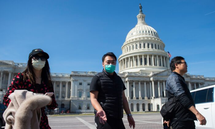 A tour operator, wearing a protective mask, gestures as he leads a tour near the US Capitol in Washington on March 9, 2020. (Andrew Caballero-Reynolds/AFP via Getty Images)
