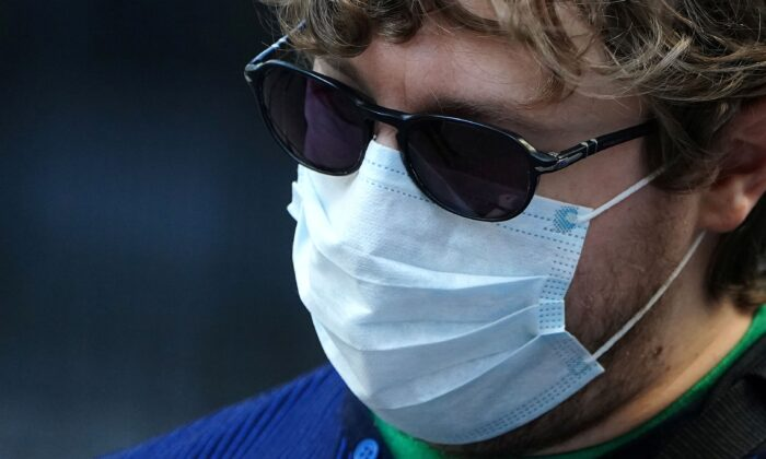 A man wearing a mask to protect against coronavirus takes pictures at the New York Stock exchange (NYSE) in the Manhattan borough of New York City, New York on March 9, 2020. (Carlo Allegri/Reuters)