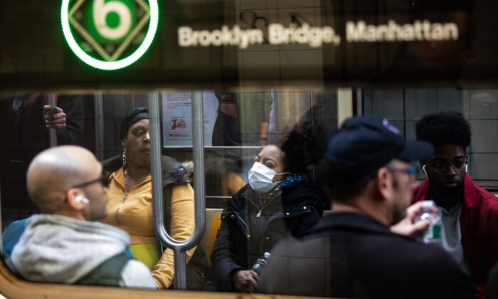 A woman wearing a protective mask rides a subway in New York City on March 9, 2020. (Jeenah Moon/Getty Images)
