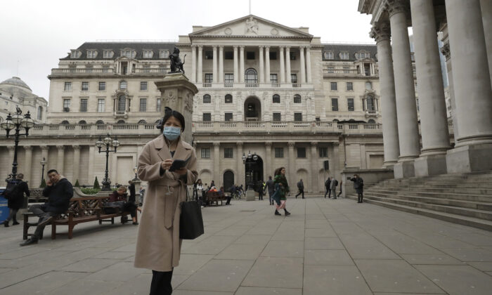 A pedestrian wearing a protective mask walks past the Bank of England in London on March 11, 2020. (Matt Dunham/AP Photo)