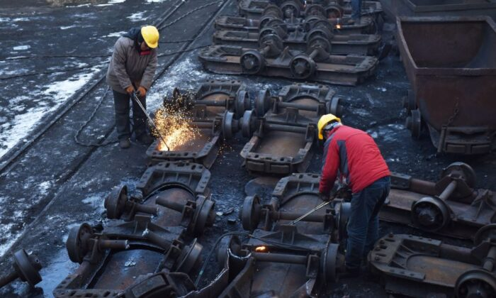 Workers cut up coal carts at the Datai coal mine in Mentougou, west of Beijing, on Dec. 18, 2019. (Greg BakerAFP via Getty Images)