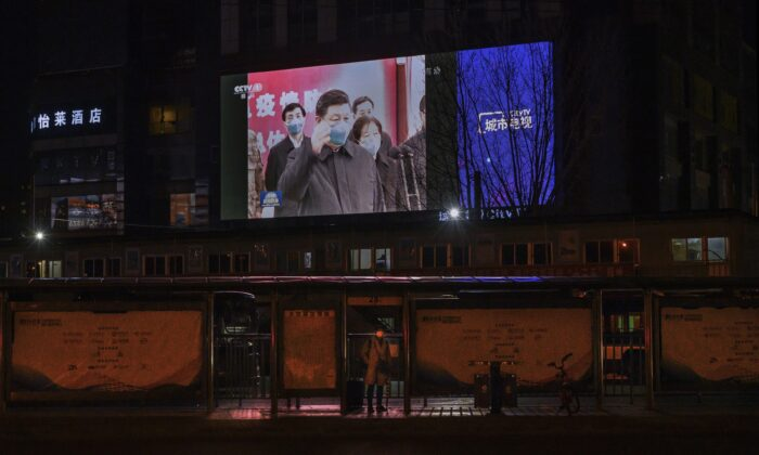 A large screen in the street shows Chinese leader Xi Jinping wearing a protective mask during his visit to Wuhan, the epicentre of the coronavirus, on CCTV's evening newscast in Beijing on March 10, 2020. (Kevin Frayer/Getty Images)