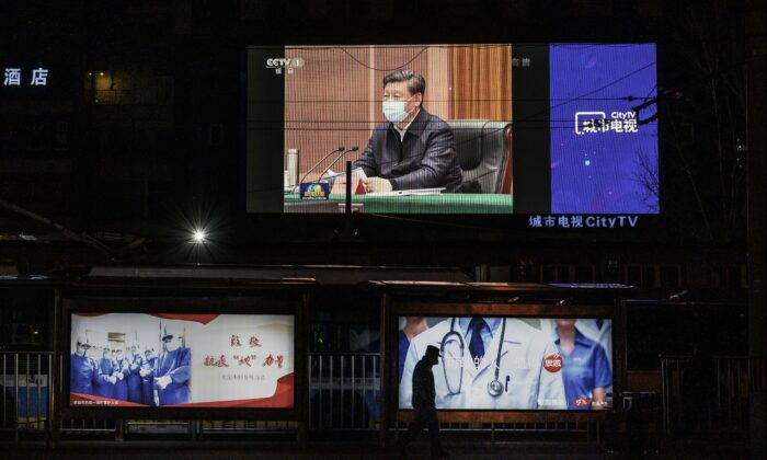 A large screen shows Chinese leader Xi Jinping wearing a protective mask during his visit to Wuhan, on CCTV's evening newscast, on March 10, 2020. (Kevin Frayer/Getty Images)