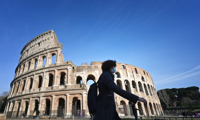 A tourist wearing a respiratory mask as part of precautionary measures against the spread of the COVID-19 coronavirus, walks past the closed Colosseum monument in Rome, Italy, on March 10, 2020. (Alberto Pizzoli/AFP via Getty Images)