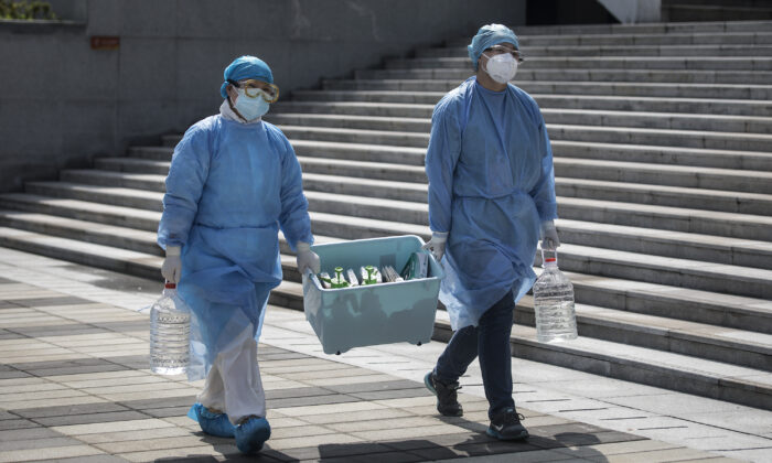 Medical workers carry a box in Wuhan, Hubei Province, China, on March 10, 2020. (Stringer/Getty Images)
