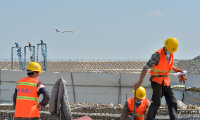 Workers wearing face masks are seen at a construction site for the expansion of Guiyang Longdongbao International Airport as an airplane flies over, in Guiyang, Guizhou Province, China, on March 8, 2020. (China Daily via Reuters)
