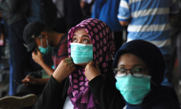 People wearing face masks wait at a train station in Bandung, in Indonesia's West Java on March 5, 2020. (Timur Matahari/AFP via Getty Images)