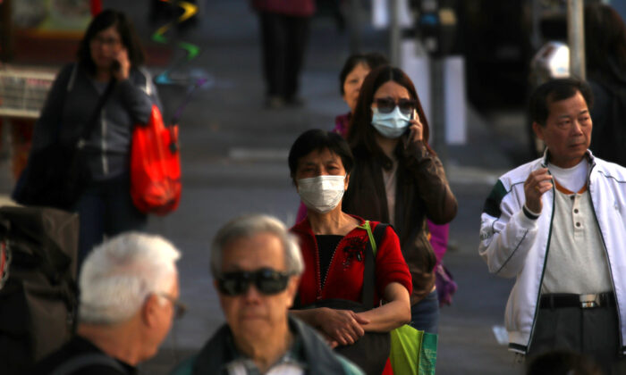 People wear surgical masks as they walk along Chinatown's Grant Avenue in San Francisco, California, on Feb. 26, 2020. (Justin Sullivan/Getty Images)