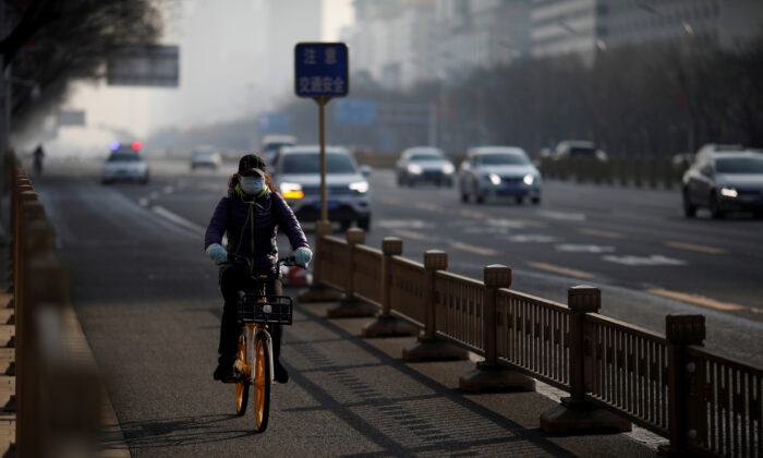 A woman wearing a face mask rides a shared bicycle on a main road in central Beijing in the morning after the extended Lunar New Year holiday caused by the novel coronavirus outbreak, on Feb. 10, 2020. (Carlos Garcia Rawlins/Reuters)