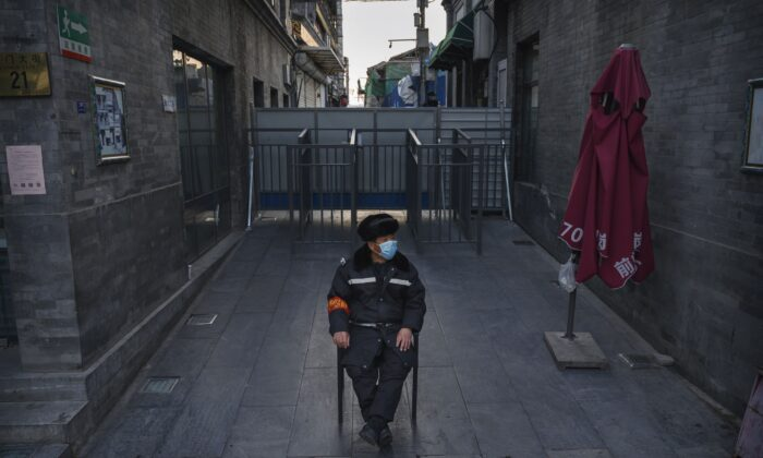A Chinese guard wears a face mask as he watches an area near a barricade blocking a residential community from a commercial area in Beijing on March 11, 2020. (Kevin Frayer/Getty Images)